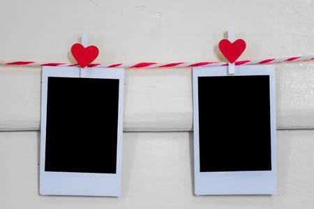 pack string: 2 Blank instant photo and red clip paper heart hanging on the clothesline with wood background.Designer concept.