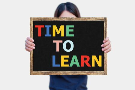 time frame: TIME TO LEARN message on the blackboard wooden frame on hand woman with white background. Stock Photo