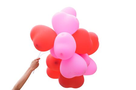 spaciousness: Hand holding red and pink balloon on white backgroundIsolated. Stock Photo