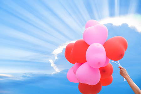 spaciousness: Hand holding red and pink balloon on blue sky for backgroundtexture.