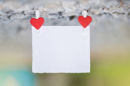Blank white paper and red clip paper heart hanging on the many stone with bokeh nature background.Designer concept.