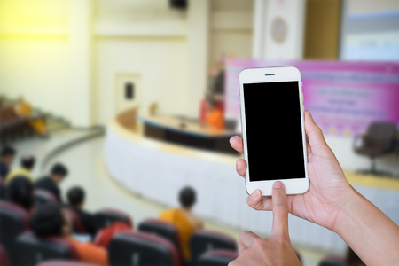 telephone poles: Hands woman holding touch screen smart phone,tablet on blurred  audience at the conference hall background.