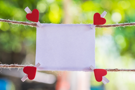 Blank white paper and red clip paper heart hanging on the clothesline with bokeh nature background.Designer concept. Stock Photo