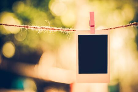 Blank instant photo and clippaper hanging on the clothesline with bokeh nature background.Designer concept.Vintage or retro tone.
