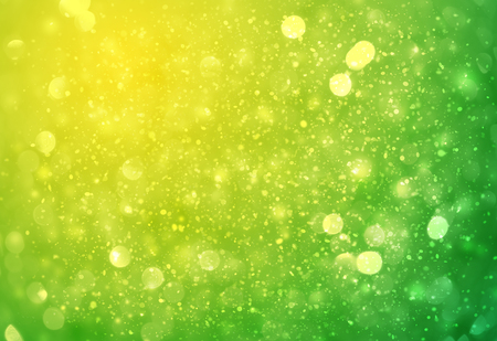 Green and Yellow sparkle rays lights with bokeh elegant abstract background. Dust sparks in explosion background. Vintage or retro. Imagens
