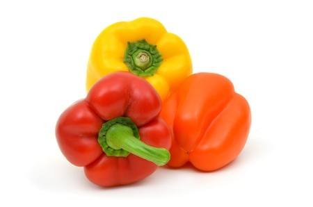 Three peppers - red, orange, yellow - on a white background photo