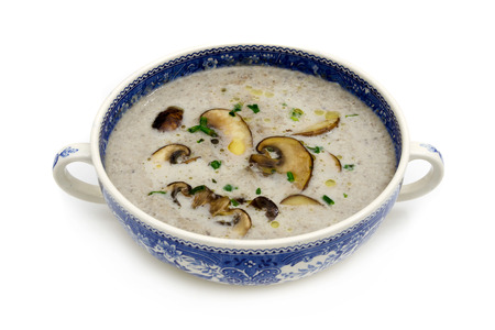 A cup of soup with mushroom soup on white background Standard-Bild