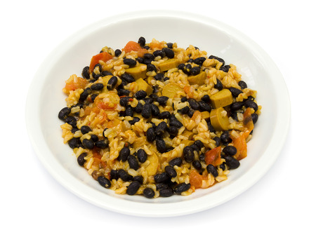 Black beans with rice, tomatoes and sausage on a white plate