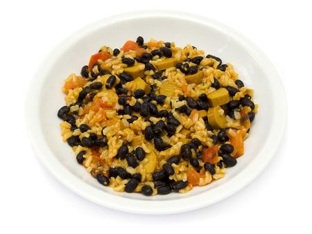 Schwarze Bohnen mit Reis, Tomaten und Wurst auf einem weißen Teller