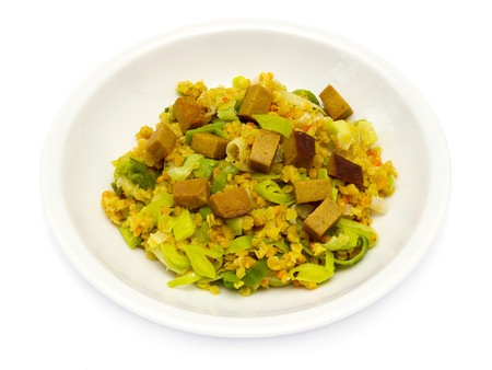 Red lentils with leeks and smoked pork on a white plate Standard-Bild
