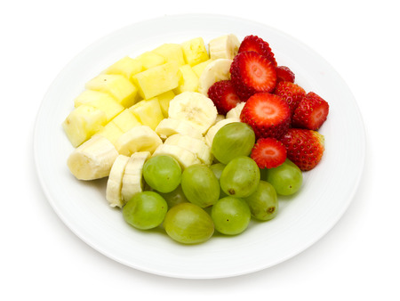 Fruit plate with bananas, pineapple, grapes, strawberries on white background