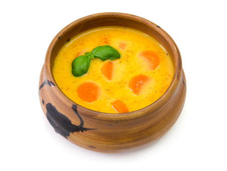A soup bowl of carrot soup with basil leaves on white background
