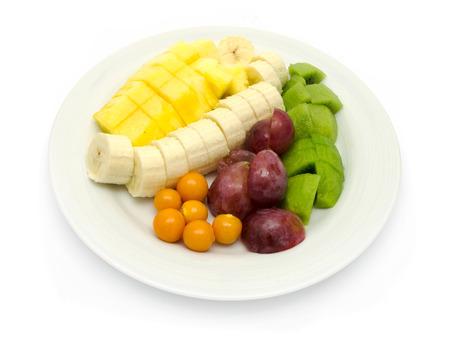 Obstteller mit Bananen, Ananas, roten Trauben, Physalis, Kiwi auf weißem Hintergrund