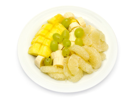 Fruit plate with bananas, pineapple, grapes, sweetie  oroblanco  on white background Standard-Bild