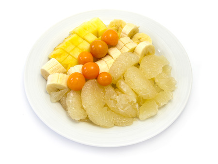 Fruit plate with bananas, pineapple, physalis, sweetie  oroblanco  on white background