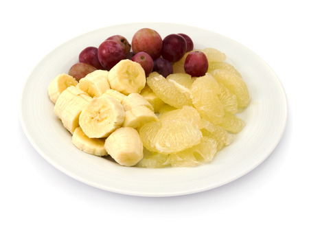 Fruit plate with bananas, sweetie  oroblanco , red grapes on white background