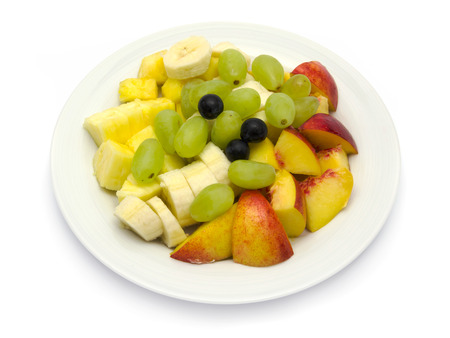 Fruit plate with bananas, pineapple, grapes, nectarines, blueberries on white background Standard-Bild