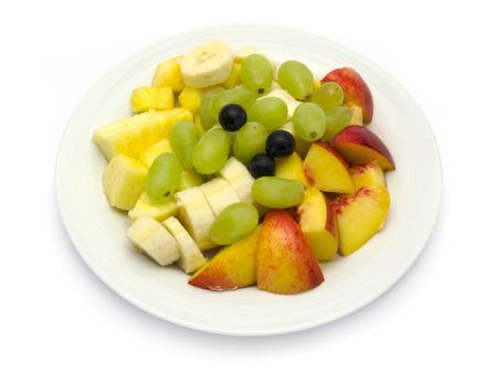 Obstteller mit Bananen, Ananas, Trauben, Nektarinen, Heidelbeeren auf weißem Hintergrund