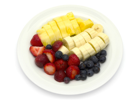 Fruit plate with bananas, pineapple, blueberries, strawberries on white background