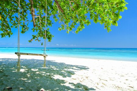 Swing On White Beach With Blue Ocean and Blue Sky