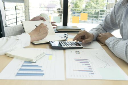 Company employees are checking the company's finances to prepare business development. Stock Photo