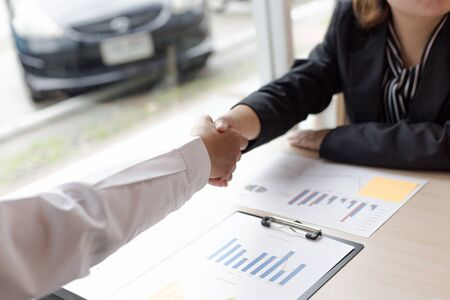 Successful in business, the company president congratulated the company secretary because of the profit from the money business, Shake hand