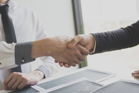 Shake hands of businessmen, young men, the company's financial accountants join hands to congratulate the owners of successful companies that are very profitable, financial business