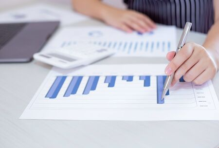 Business financial and investment concepts, people using calculators and data graphs to analyze company revenue and expenditures in preparation for the planning of presentations, finances concept