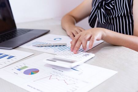 Business financial and investment concepts, people using calculators and data graphs to analyze company revenue and expenditures in preparation for the planning of presentations, finances concept Stock fotó