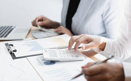 Accountants and employees are counting money and recording company revenue expenditures and calculating office investment costs, Financial concepts, Bank accounting.