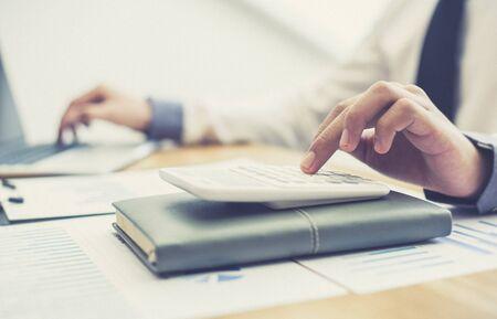 Les hommes d'affaires utilisent des calculatrices pour calculer les impôts et les revenus de l'entreprise au bureau, les concepts bancaires financiers et comptables. Banque d'images