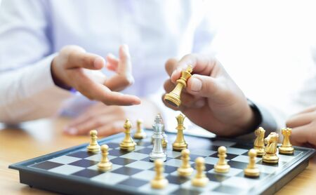 Business men and women analyze chess playing strategies to reduce risks and achieve success, Management or leadership concept. Imagens