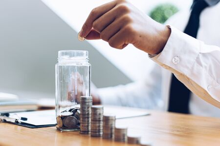 Hold a coin in a glass, Businessmen prepare a financial plan by accounting income - expenses for stable business growth saving ideas, Saving money concept