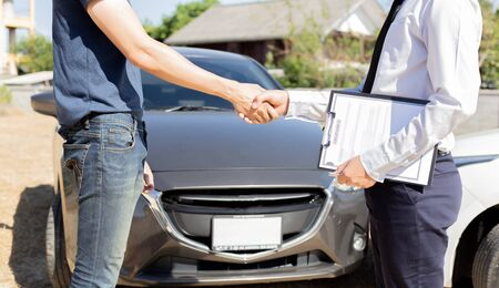 Customers shake hand with car insurance agents to enter into friendly terms and conditions, Car crash on the road concept. Imagens
