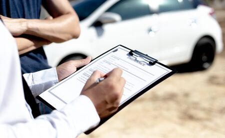 Insurance agents inspect for damage to cars that collide on the road to claim compensation from driving accidents, Insurance concept.
