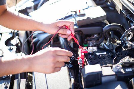 Auto repair technician has inspected the condition of the engine using ammeter, Car repair service concept. Foto de archivo