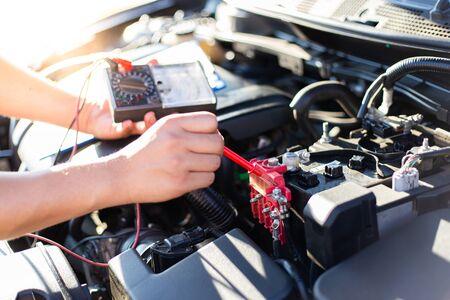 Der Autoreparaturtechniker hat den Zustand des Motors mit dem Amperemeter, dem Autoreparaturservice-Konzept, überprüft. Standard-Bild