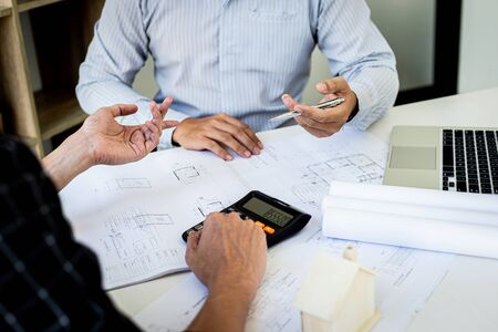 Engineers or architects are meeting a team to design the architectural structure in the design with blueprints and model buildings in working site, Technological structure and construction Concept. Stock Photo