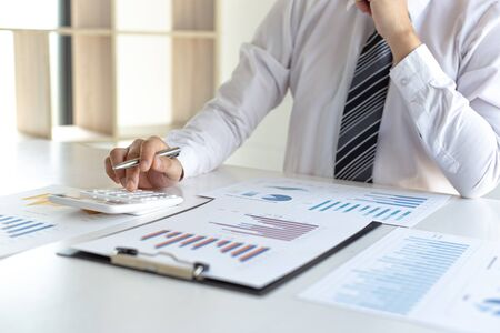 Business men are calculating real estate investment expenditures and analyzing the company's finances in line with the global economy, Analysis of financial accounting and real estate investment concept.
