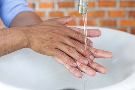 Young man is washing his hands in a sink sanitizing the colona virus for sanitation and reducing the spread of COVID-19 spreading throughout the world, Hygiene ,Sanitation concept.