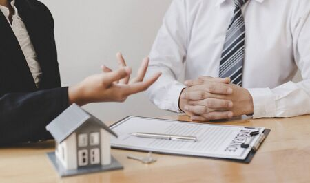 Real estate broker agents advise clients to make a decision to buy a house with insurance. Negotiating purchase-sale and investment planning concept. 版權商用圖片