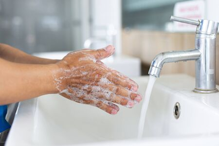 Man is washing his hands in a sink sanitizing the colona virus for sanitation and reducing the spread of COVID-19 spreading throughout the world, Hygiene ,Sanitation concept.