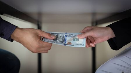 Businessmen give dollars to bribe employees in signing contracts to buy illegal land and real estate, Business fraud and social injustice, corruption and bribery concept.