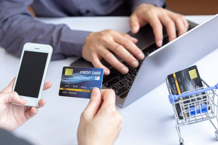 Both business people use laptop and phones to register online purchases using credit card payments, Convenience in the world of technology and the internet, Shopping online and banking online concept.