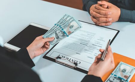 Businessmen give dollars to bribe employees in signing contracts to buy illegal land and real estate, Business fraud and social injustice, corruption and bribery concept. Banque d'images