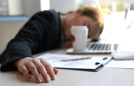 The financial accountant works on analyzing and summarizing the company's incomes and expenses in real estate and account management, causing her to get tired and fall asleep on her desk, Hard work and overtime work concept.