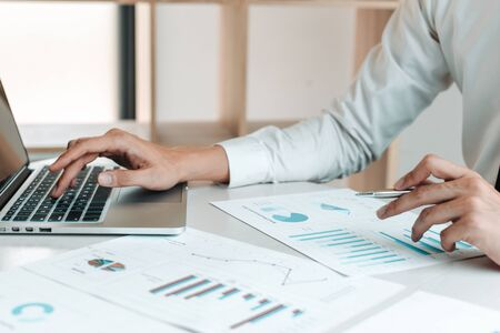 Financial businessmen use laptop to analyze marketing strategies and real estate data to reduce company taxes for their customers, Accounting and Tax concept.