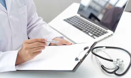 Doctor uses a laptop computer to record patient information and write it on a document to prepare for diagnosis in the room of a modern hospital, Emergency assistance and health care concept.