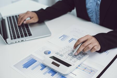 Businesswomen are calculating finances and analyzing market data with graphs and laptops at work, Business Financing Accounting Banking and tax system Concept. Banque d'images