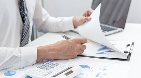 Marketing businessmen are analyzing financial and insights strategies for generating revenue including corporate income tax with laptops and graphs in the office, Finance and Accounting concept.